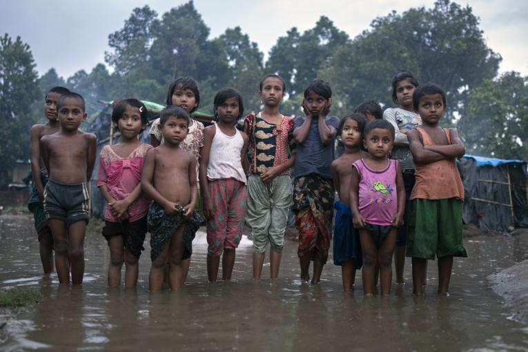 Rohingya refugee children wade through flood waters surrounding their families' shelters following an intense pre-monsoon wind and rain storm in Shamlapur Makeshift Settlement, Cox's Bazar district, Bangladesh on 20 May 2018.