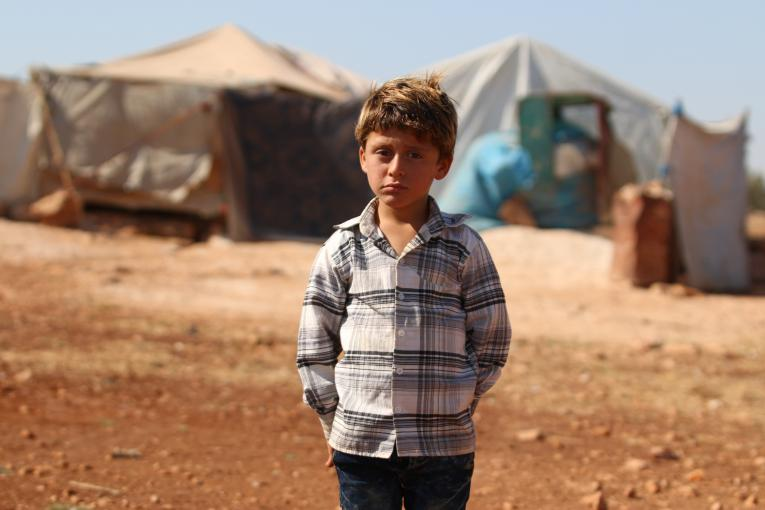 On 21 August 2018 in rural Idlib, Syrian Arab Republic, an internally displaced boy stands near his temporary shelter.