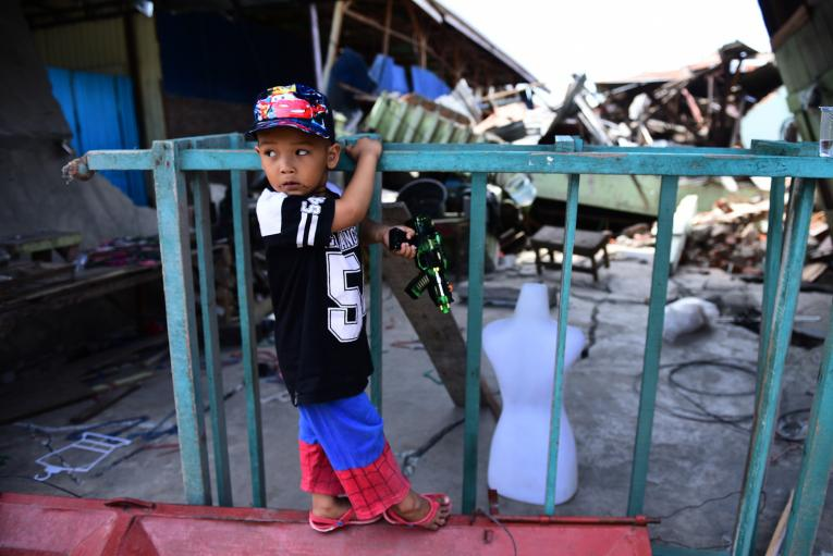On 4 October 2018 in Indonesia, Muhamad Akbar, 4 years old, plays in front of the ruins of the building damaged during the earthquake in Palu, South Sulawesi.