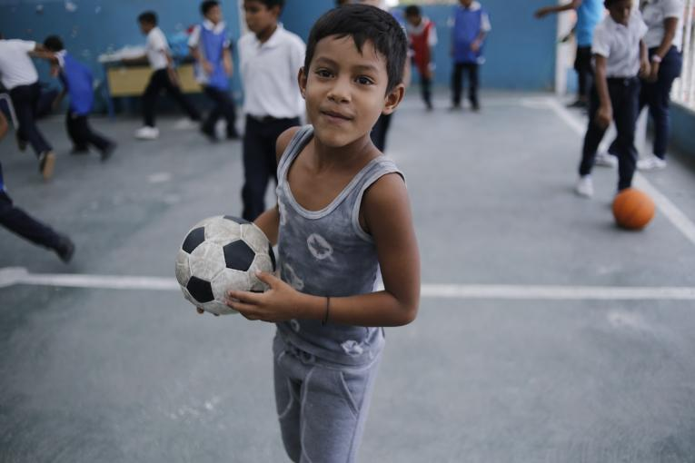 4 June 2019: A child playing on the roof of El Carmen school in Barrio Union, Petare, in the outskirts of Caracas, Venezuela. It is too dangerous to play outside and children head straight home as soon as they leave school. Even a basketball hoop right outside the school was removed to discourage children from hanging out outdoors.