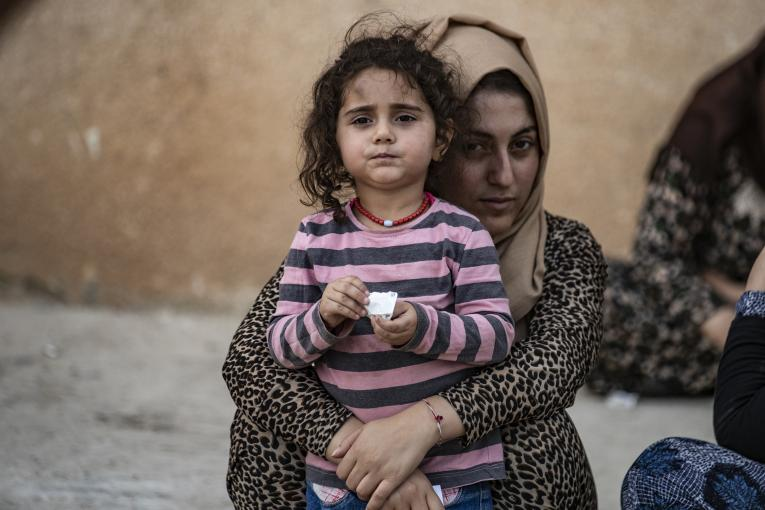 On 11 October 2019 in the Syrian Arab Republic, a woman holds a child as families displaced from Ras Al-ain arrive in Tal Tamer, 75km southeast Ras of Al-ain, having fled escalating violence.