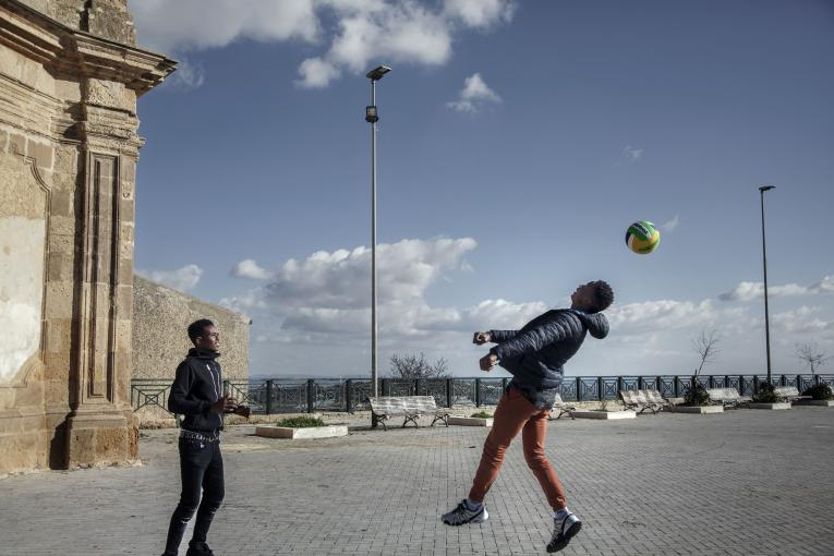 Omar (17), left, plays football with his housemate Youssouf (17) at a piazza in the small village of Naro, in Sicily, Italy. Omar migrated from Senegal and has been in Italy for about a year.