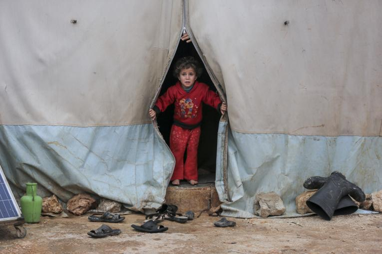 A child looks out of a tent in Kafr Losin Camp in northwest Syria on the 19 January 2021