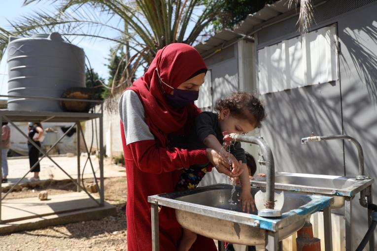 Mother Kanouz holding her one-year old daughter Fatima to wash her hands at Mhamara informal settlement, 5 July 2021