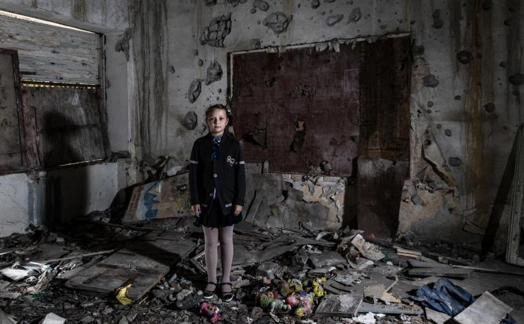 Ukraine. A child stands in a destroyed classroom.