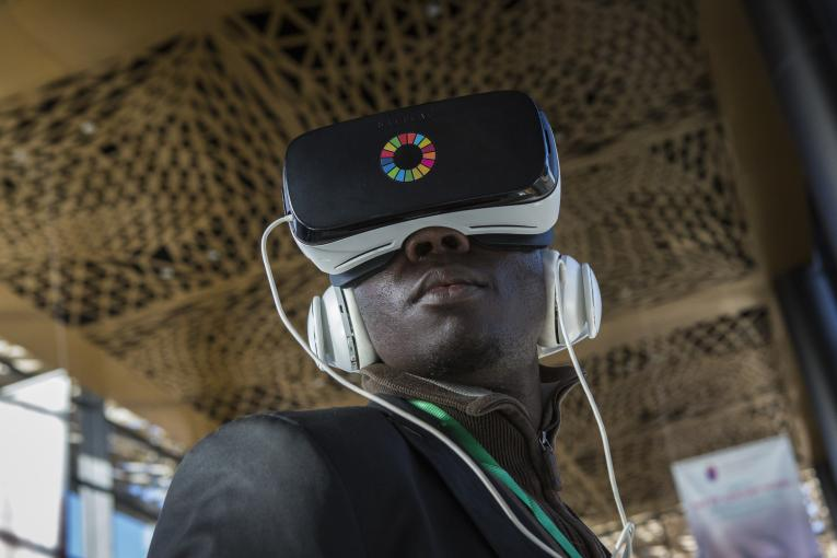 A journalist wears a headset and watches a virtual reality video at a UNICEF exhibition in Senegal