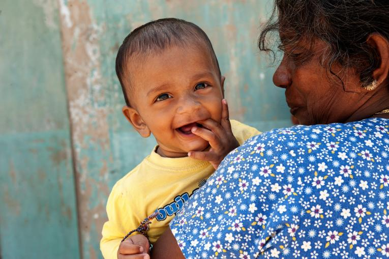 A smiling baby cared for by his mother. Sri Lanka