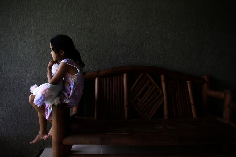 An 8-year-old girl sits in front of her home at a shelter in the Philippines.