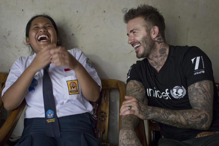 David Beckham laughing with a young girl
