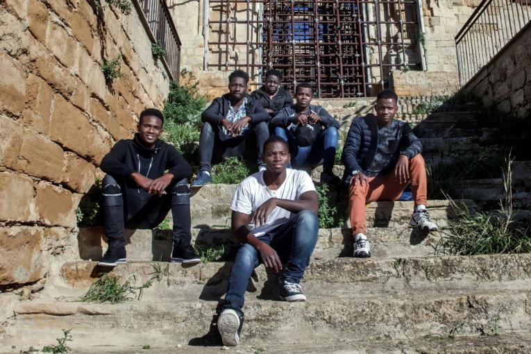 Italy. Migrants sit in a village in rural Sicily.