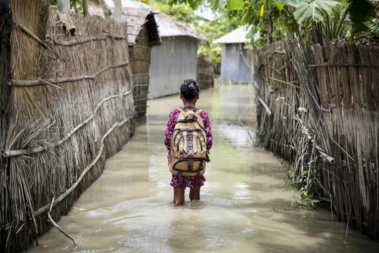 A child wades through water on her way to school in Kurigram district of northern Bangladesh during floods in August 2016.