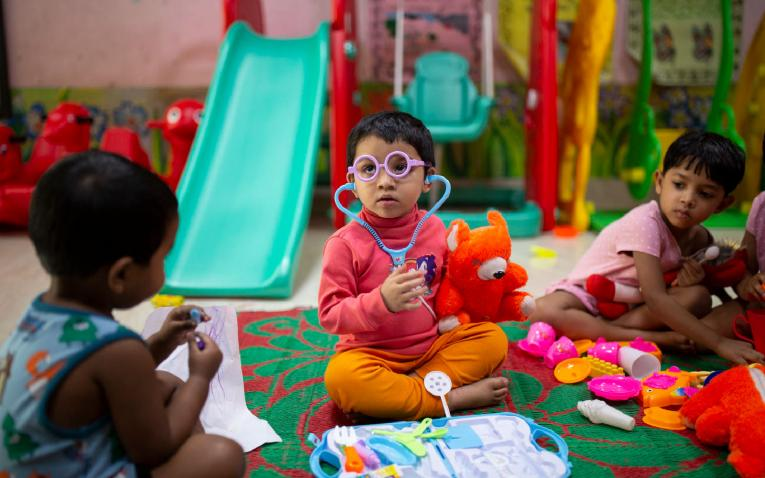 A child wearing a toy medical kit sits on the floor of an Early Childhood Devleopment Centre in Bangladesh