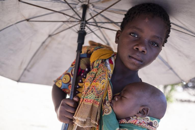 Mozambique. A girl holds her baby brother.