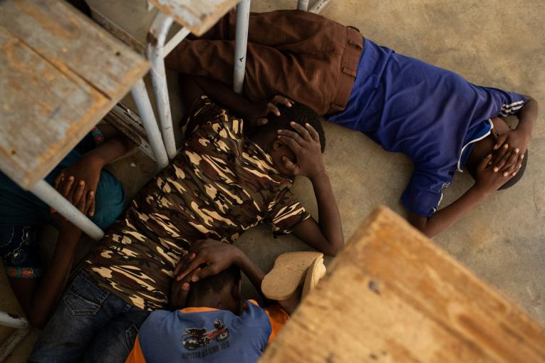 On 26 June 2019, children take part in an emergency attack simulation, as they practice sheltering and evacuation in the event of an armed attack, at the Yalgho Primary School in Dori, Burkina Faso.