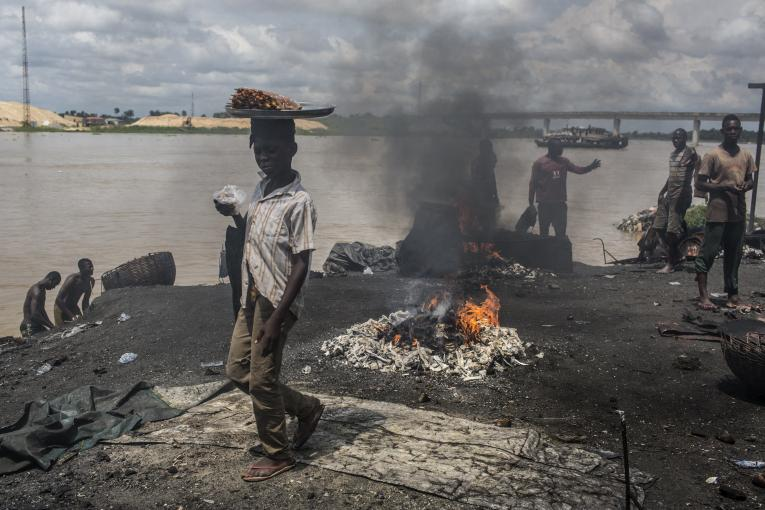 On 24 October 2016 in Yenagoa, Bayelsa State, Nigeria, children pass in front of a flame fed by waste and rubber materials in order to make Kanda, a type of smoked meat, at an abattoir. The workers at the slaughterhouse use cow bones, rubber tires, electric wires, aluminum cans and other waste to sustain the flames, making the fumes very dangerous to inhale.