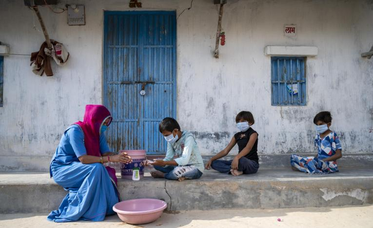 A mother and her children wash their hands outside their home using a bucket, water, and soap.