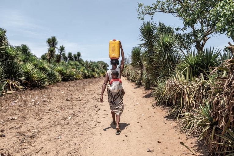 Mother and child walking with water jug.