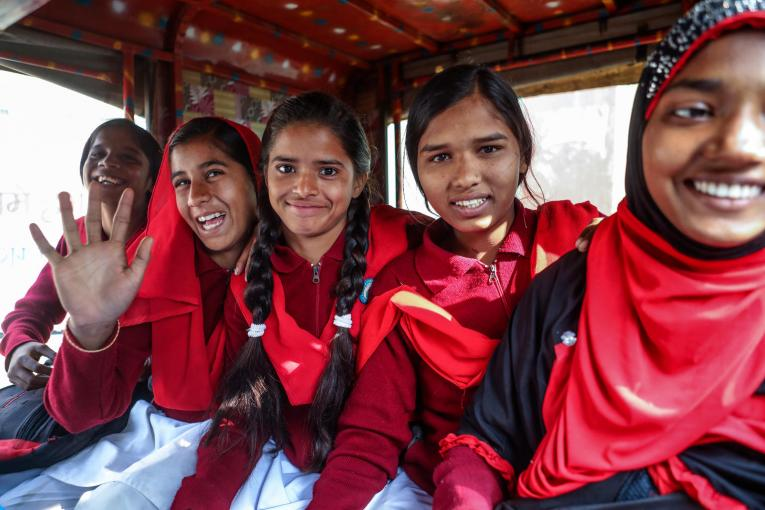 Girls sitting in a row smiling - India