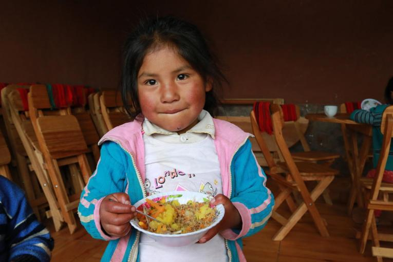 A girl eats lunch in Peru