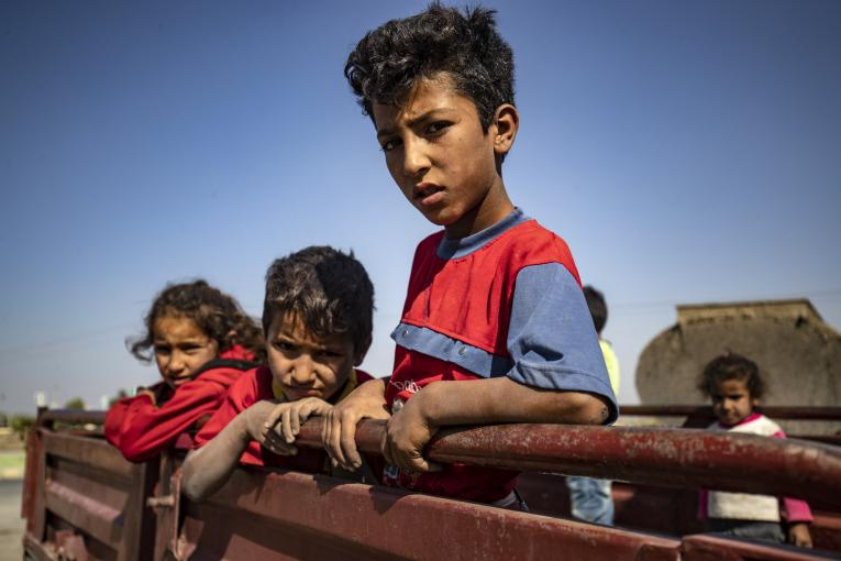 Syria. Children stand on the back of a truck.