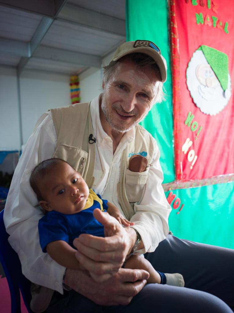 Liam Neeson holds 3-month-old boy in Brazil