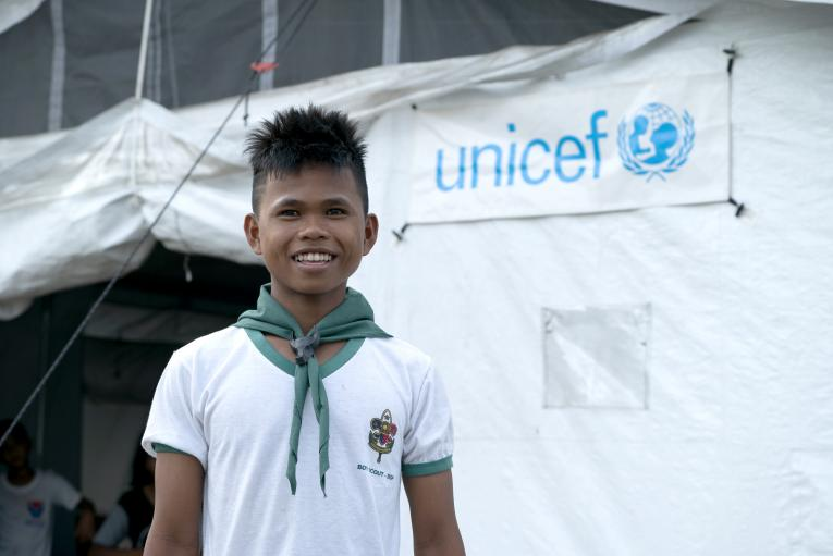 Philippines. A boy stands outside a prototype High Performance Tent.