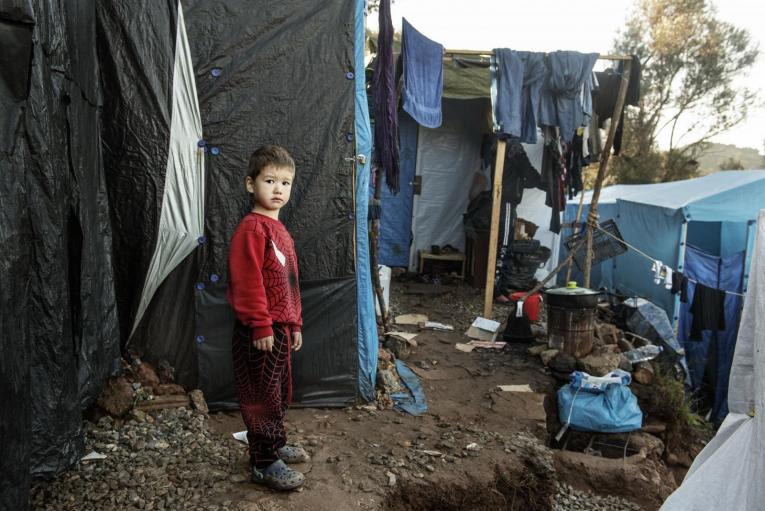 Greece. A child stands near a tent.