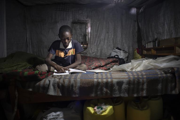 Rafael, 11, studies his Class 6 textbooks and revises the exercises in Kenya.