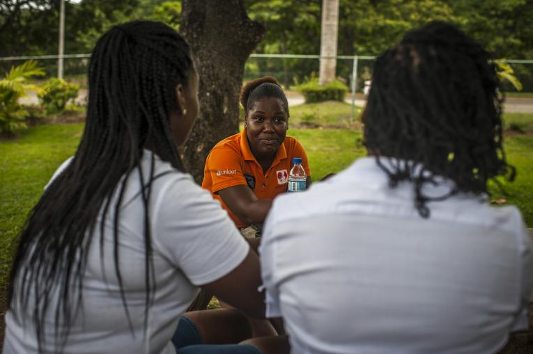 On 12 June 2018 in Jamaica, EVE for Life mentor Monique McDonald, 27, speaks with (left) Shelly, 22, and (right) Stacy-Ann Stone, 38, in a public park in Ocho Rios town.