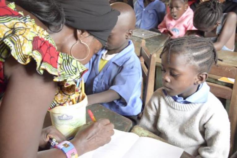 A teacher writes with a student, Central African Republic
