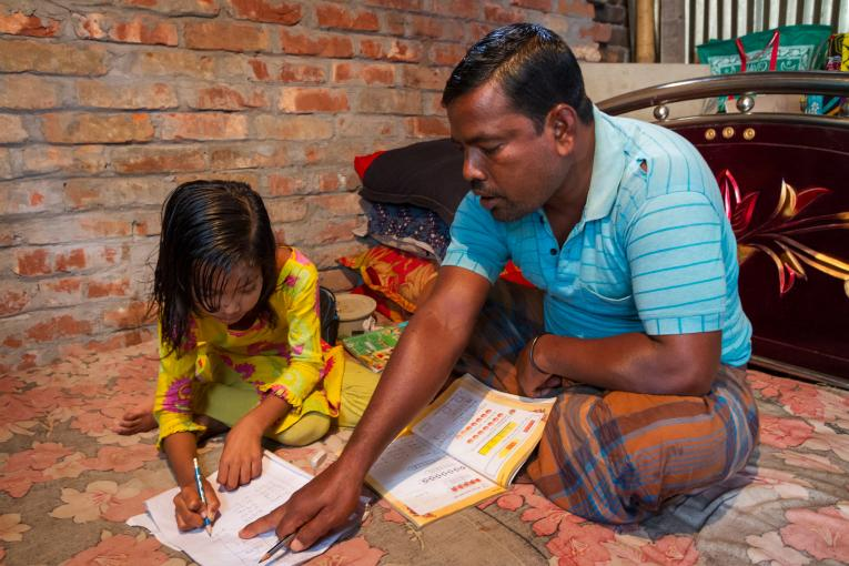 Azharul Islam, 45, works with his seven-year-old daughter Aduri on her homework