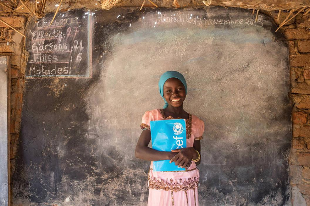 Girl smiling holding a UNICEF book