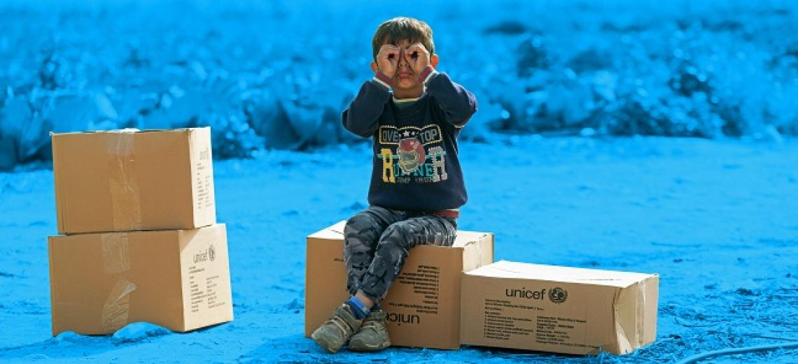 A young boy sitting on top of UNICEF box.