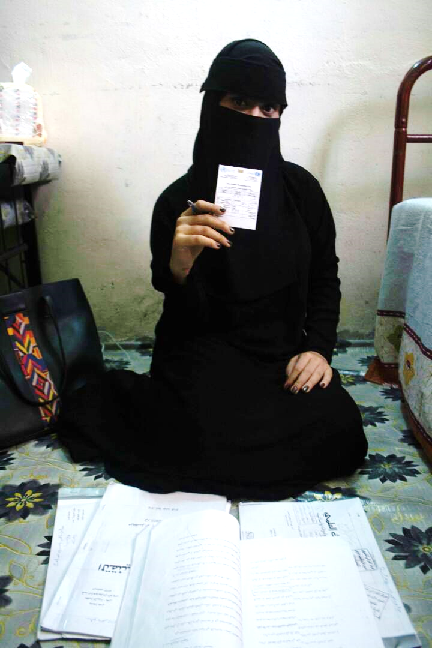 A girl holds up a vaccination card, Yemen