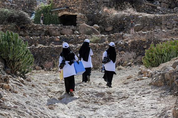 Three women walk through a mountain village carrying vaccination supplies