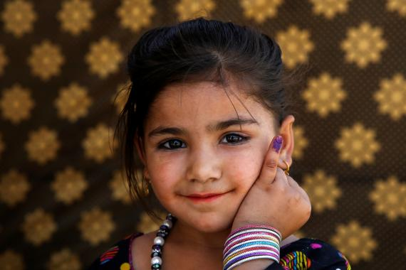 A girl shows the ink mark on her finger indicating she has received a polio vaccine, Pakistan.