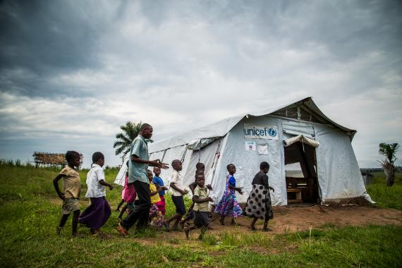 A teacher accompanies his students to their class in a temporary tent school in the Kasai region, Democratic Republic of the Congo, DRC.