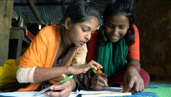 Two girls write on a sheet of paper, Bangladesh