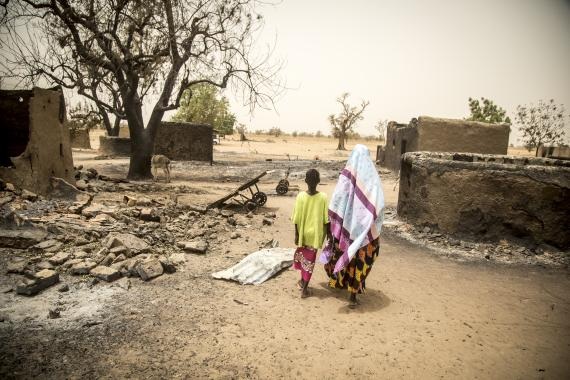 Mali. A woman and daughter walk through the remains of their village.