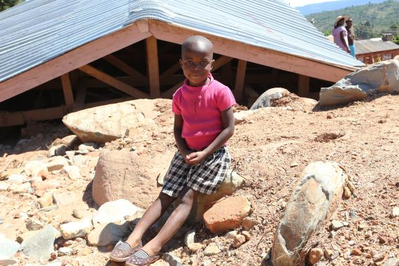Zimbabwe. A girl sits in front of the remains of her home.