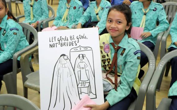 "A girl in a girl guides uniform in Malyasia holding a sign saying ""let girls be girls, not brides"""