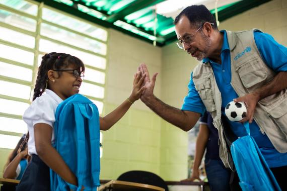 A UNICEF staff member gives a high five to a schoolgirl holding a UNICEF schoolbag