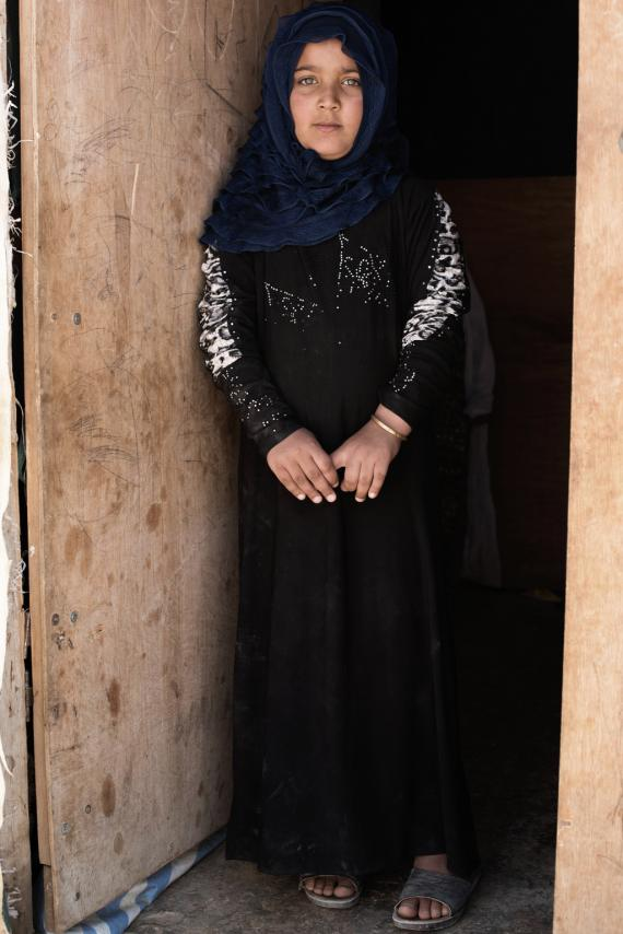 Dyana stands for a photo in the doorway of a shelter