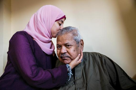 A woman holds and kisses her father on his head