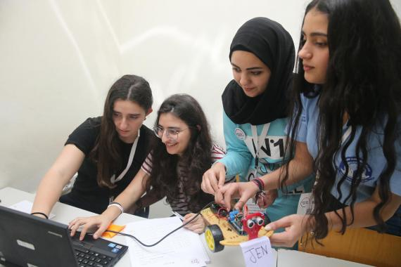 A group of teenage girls holding a small robot looking at a laptop screen