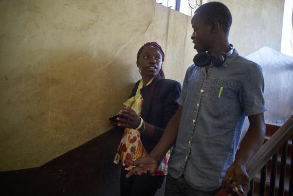 Dawwing Ouma climbs down stairs of his apartment with Laura Adema, both Sauti Skika coordinator for Kisumu County, in the city of Kisumu. Kenya