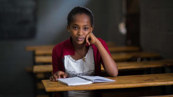 A teenage girl sits at a desk, Ethiopia
