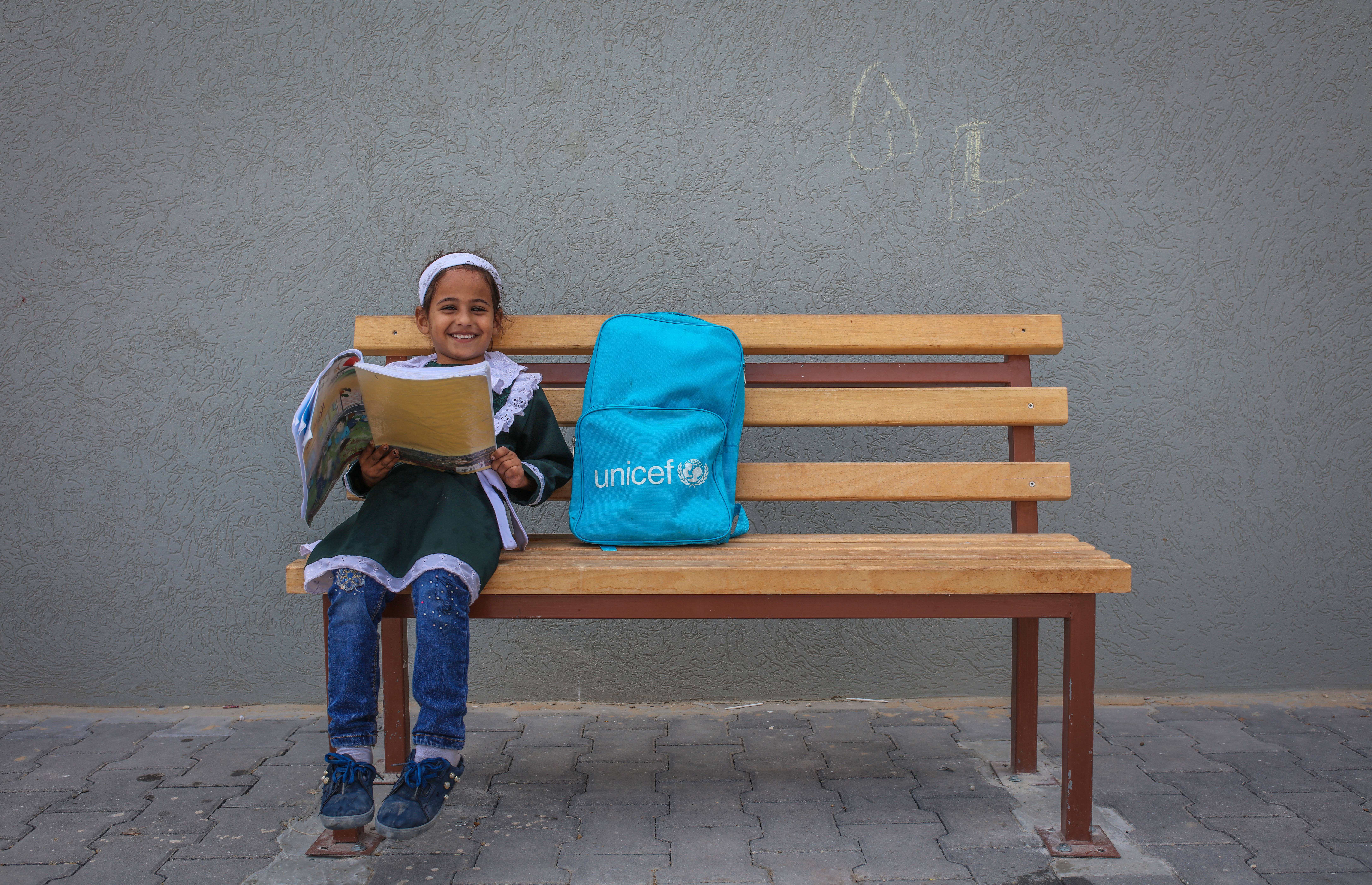 Girl sitting near bag