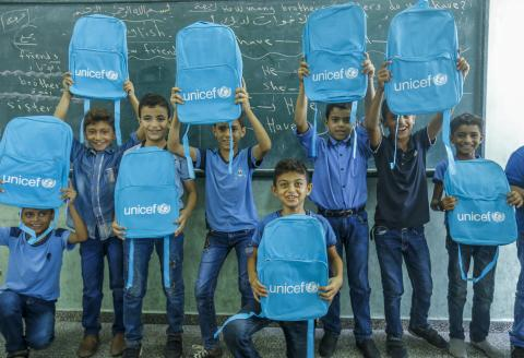 Boys holding UNICEF's bags