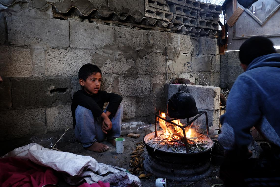 14-year old Feras makes a fire in the family home. In dry weather the family often cooks in a little space on top of the kitchen to save on gas.